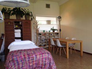 U ziet hier een foto van de praktijkruimte, je ziet een behandelbank en een vergadertafel met vier stoelen. Het is een lichte en zonnige ruimte en rond vier meter hoog